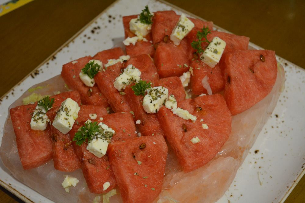Watermelon and feta cheese salad on a Himalayan salt block